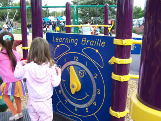 "Girls playing with ""Learning Braille"" clock on accessible playground"